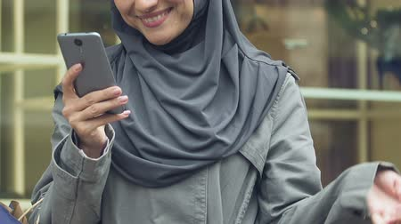 delighted : Arab woman typing message on smartphone, boasting to friends about purchases Stock Footage