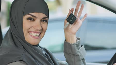 islámský : Muslim woman showing keys, excited with car purchase, driving gender equality