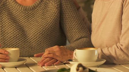 bereavement : Woman stroking friend hand in support, two sisters experiencing grief together Stock Footage