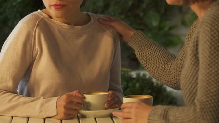 klagen : Women communicating over cup of coffee, telling secrets, supporting in grief