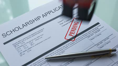 в ожидании : Scholarship application document pending, hand stamping seal on official paper