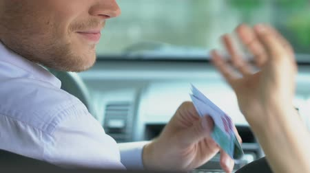 fare : Friendly cab driver taking money from client, taxi service, transportation Stock Footage