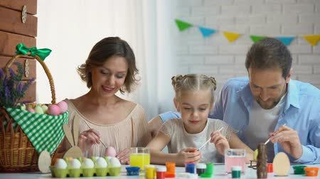 easter : Beautiful family decorating Easter eggs with colorful paint, ancient traditions