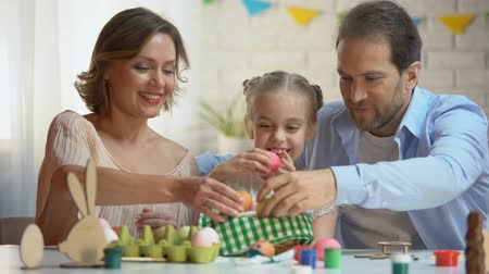 easter : Beautiful family putting dyed Easter eggs into basket, Christians traditions