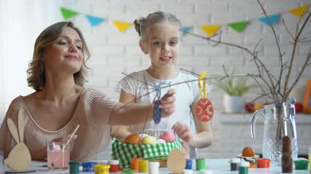 easter : Mommy and daughter decorating branches with hand-made toys, Easter traditions Stock Footage