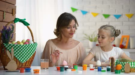 hard boiled : Mom teaching daughter how to color Easter eggs, family preparing for holiday Stock Footage