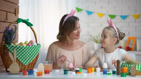saç bantı : Little daughter kissing mother on cheek helping with Easter eggs decor, love