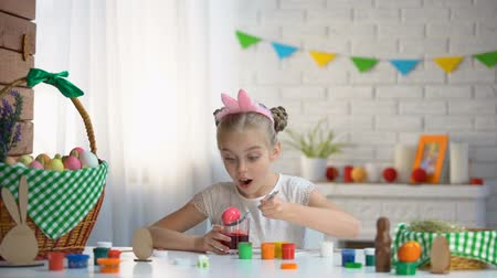 hristiyanlık : Small girl practicing in eggs coloring, hostess preparing for Easter, traditions