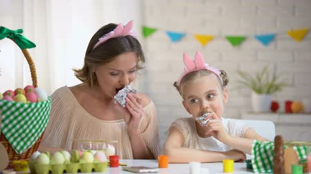 euforia : Beautiful mother and daughter in funny headbands eating Easter chocolate eggs