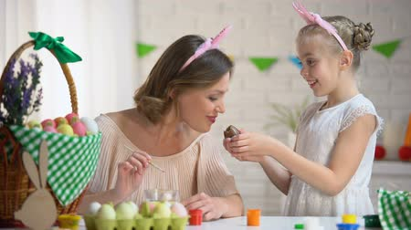 eufória : Little girl sharing with mother chocolate egg, proper upbringing, Easter coming
