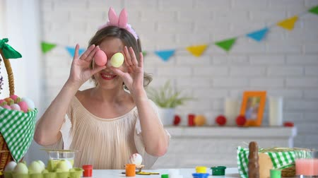 regozijo : Smiling woman having fun holding colorful Easter eggs near her eyes.