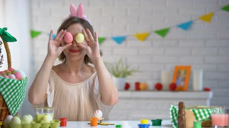 headband : Cheerful woman putting Easter eggs to eyes having fun and enjoying bright fest