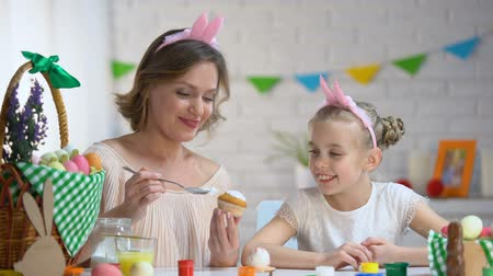 fırınlama : Mother and daughter icing home-made cakes and decorating them with sprinkles Stok Video