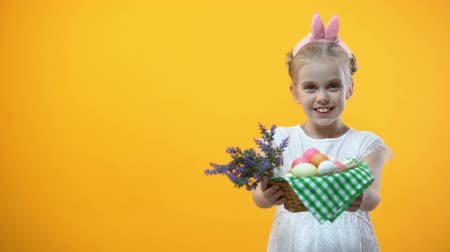 húsvét : Smiling little kid showing basket with colorful eggs yellow background, Easter