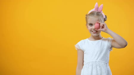 auguri pasqua : Playful female kid holding colored egg in front of eye, Easter symbol, holiday Filmati Stock