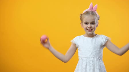 saç bantı : Happy little girl holding colored Easter eggs in front eyes and smiling camera Stok Video