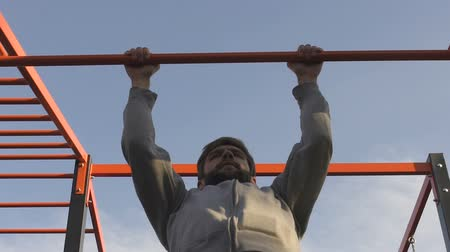 pulling up : Bearded man pulling-up on crossbar, morning exercises, source of energy, sport