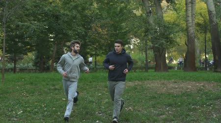kardiyo : Two male friends jogging in park early in morning, fitness exercises, lifestyle