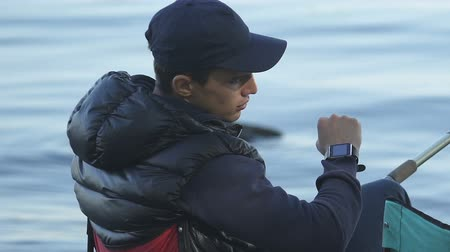 návnada : Young fisherman looking at his smart watch, checking time and temperature