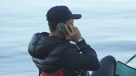 низкий : Man answering phone call during fishing, poor connection, communication quality