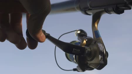отдыха : Man winding fishing line on spinning reel, professional equipment, close-up