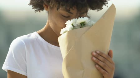 camomila : Happy biracial female holding bouquet of white flowers and sincerely smiling