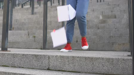 písanka : Young woman going down stairs and dropping her notebooks, picking them up
