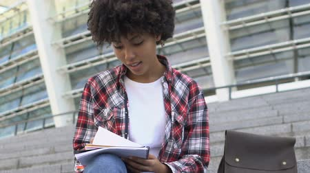 foreigner : Curly-haired biracial girl sitting on stairs and writing something in notebook