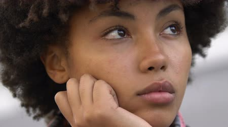nejistota : Curly-haired afro-american girl thinking about life important things, close-up