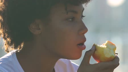 potraviny : Beautiful african american woman eating apple on city street, healthy snacks