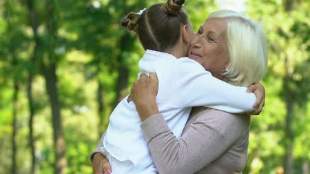 sarılmak : Little cute girl tightly hugging her grandmother in day park, family weekend Stok Video