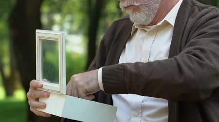 fame : Old grey-haired veteran opening box with medal, unhappy war time memories Stock Footage