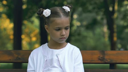oppression : Sad lonely little girl sitting on bench in park, bullying and cruelty at school