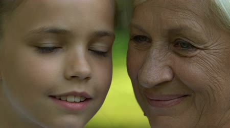 leisure time : Granny and granddaughter looking at each other, posing for camera, close up Stock Footage