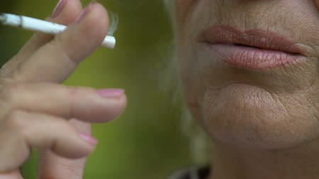 smoke kills : Senior wrinkled woman smoking cigarette, close up, fighting cancer concept Stock Footage