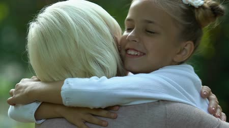 ailelerin : Little girl hugging her grandmother and kissing on cheek, family care and love