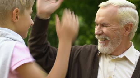 gest : Cute boy giving high five to his old grandfather while they having rest in park Stock Footage