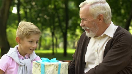 moudrý : Grandfather presenting birthday giftbox to his grandson, celebration, happiness Dostupné videozáznamy