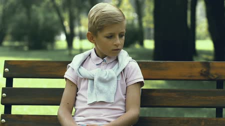 grim : Unhappy little boy sitting alone on bench in park, school bullying and cruelty