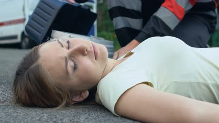 faint : Unconscious woman lying on asphalt, paramedic rendering first medical assistance Stock Footage
