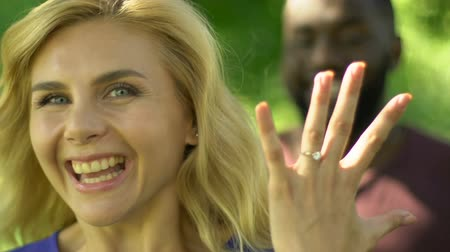 regozijo : Happy blonde woman showing hand with expensive engagement ring, making proposal