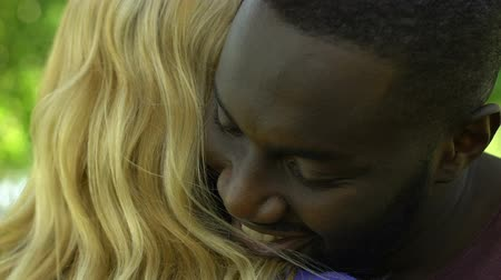прижиматься : Happy african-american man hugging his pretty blonde girlfriend, close up