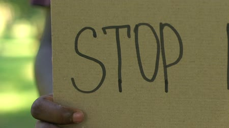ret : Stop racism phrase written on template holding african-american man, concept