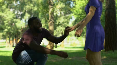 proposta : Afro-american man making proposal to girlfriend while they walking in park