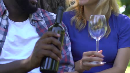 бокал : Afro-american male pouring wine to girlfriends glass, romantic outdoor date Стоковые видеозаписи