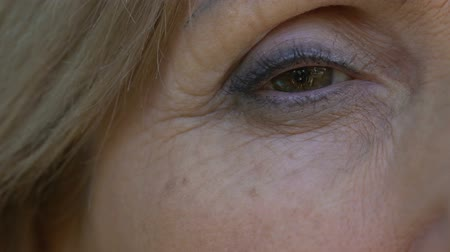 nyomasztó : Close-up eye of senior lady, recollects lived years and events, aging, memories