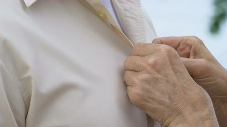 buttoning : Mature caring lady adjusting buttons on husband shirt, togetherness and love