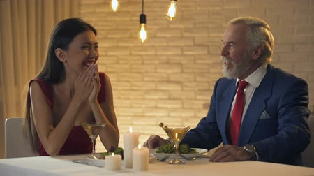 kíséret : Beautiful lady laughing and flirting with old rich man in restaurant, escort