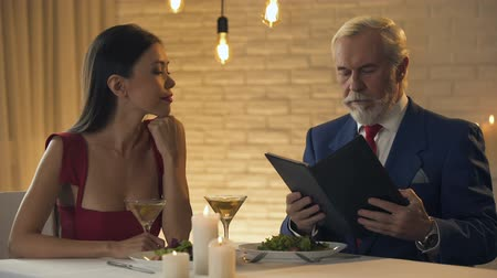 feedback geven : Greedy male shocked with high prices in luxury restaurant bill, romantic dinner Stockvideo