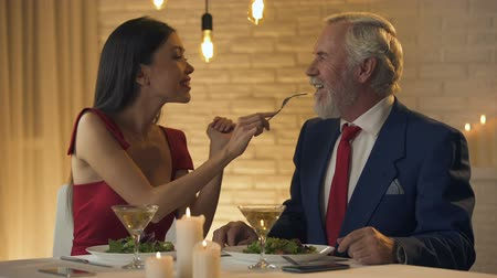 darling : Sexy young woman flirting with old millionaire, feeding him in restaurant